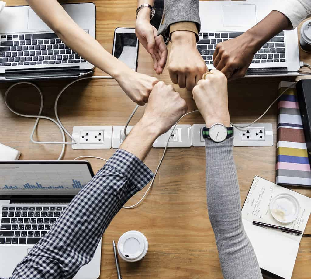 6 people putting their hands together at the center of a desk symbolizing teamwork